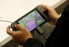 Nintendo Co Ltd puso el viernes un precio por encima de las expectativas del mercado a su primera consola en cuatro años, decepcionando a los inversores y reduciendo sus perspectivas de recuperar a unos jugadores que han pasado de las consolas a los teléfonos inteligentes. En la foto, un hombre juega con la nueva consola Switch en Tokio el 13 de enero de 2017. REUTERS/Kim Kyung-Hoon