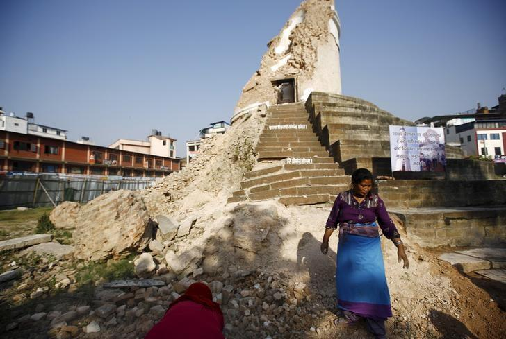 Women clean the premises of the historic nine-storey Dharara tower during the first anniversary of the earthquake in Kathmandu, Nepal, April 24, 2016. REUTERS/Navesh Chitrakar/Files