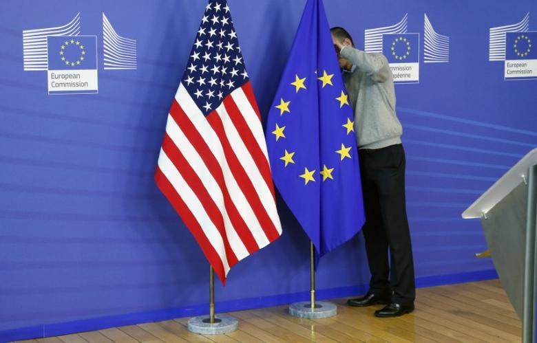 A worker adjusts European Union and U.S. flags at the start of the 2nd round of EU-US trade negotiations for Transatlantic Trade and Investment Partnership at the EU Commission headquarters in Brussels November 11, 2013. REUTERS/Francois Lenoir