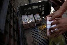 Pilas de billetes de 100 bolívares en una cesta de plástico en un mercado en Caracas.  16 de diciembre de 2016. Pilas de billetes de 100 bolívares en una cesta de plástico en un mercado en Caracas REUTERS/Marco Bello