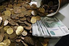 Рублевые монеты и купюры. Рубль в понедельник утром показывает незначительную позитивную динамику в начинающийся сегодня налоговый период с оглядкой на форекс при малоподвижном нефтяном рынке.  REUTERS/Ilya Naymushin (RUSSIA - Tags: BUSINESS)