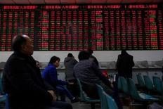 Инвесторы в брокерской конторе в Шанхае. 3 января 2017 года. Основные фондовые индексы Китая снизились пятую сессию кряду в понедельник во главе с техносектором из-за ухудшения настроений инвесторов относительно перспектив в 2017 году после комментариев премьер-министра страны и выхода данных, указавших на замедление роста экономики в крупных городах. REUTERS/Aly Song