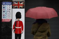 A pedestrian shelters under an umbrella as she walks past a money exchange sign in central London, Britain January 16, 2017. REUTERS/Stefan Wermuth