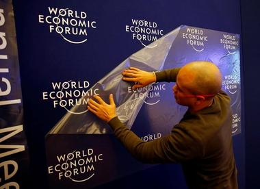 A worker prepares the logo of the World Economic Forum in the congress...