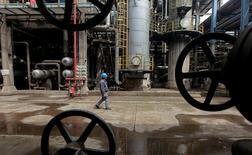 Un trabajador camina por tuberías de petroleo en Wuhan, provincia de Hubei, China. 23 de marzo 2012.La producción de crudo en China caería un 7 por ciento a 2020 en comparación al plan de cinco años previo, en la medida en que se reduzca el bombeo de algunos de los pozos más grandes y antiguos del país, mientras que el suministro de gas natural se disparará en casi dos tercios. REUTERS/Stringer/File Photo - RTSLRAT