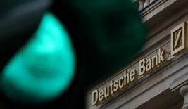FILE PHOTO: A green traffic light is seen next to the logo of Germany's largest business bank, Deutsche Bank in Frankfurt, Germany, October 27, 2016. REUTERS/Kai Pfaffenbach/File Photo