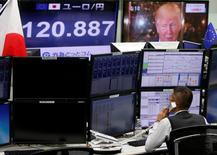 An employee of a foreign exchange trading company works near monitors showing U.S. President-elect Donald Trump (top R), and the Japanese yen's exchange rate against the euro in Tokyo, Japan, January 18, 2017.    REUTERS/Toru Hanai