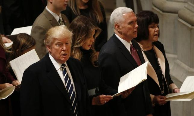 1月20日、トランプ米大統領(写真左)は、各政府機関に対しあらゆる規制の凍結を指示するとともに、オバマ前大統領の主導で成立した医療保険制度改革(オバマケア)を見直すための大統領令に署名した。 21日撮影(2017年 ロイター/Kevin Lamarque)