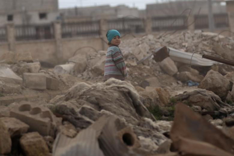 A child walks through rubble of damaged buildings in al-Rai town, northern Aleppo countryside, Syria January 20, 2017. REUTERS/Khalil Ashawi