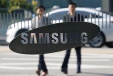 El gigante surcoreano Samsung Electronics Co Ltd dijo el martes que su beneficio operativo subió un 50 por ciento hasta su mayor nivel en más de tres años, debido a que las ganancias de su negocio de procesadores contrarrestaron el impacto negativo del fallido lanzamiento del teléfono Galaxy Note 7. En la imagen de archivo, empleados junto a un logo de Samsung en Seúl.  REUTERS/Kim Hong-Ji