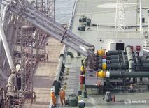 Imagen de archivo de empleados portuarios supervisando una carga de crudo en un tanquero en el puerto de Kuwait. 3 abril 2006. Los precios del petróleo subían el martes ante la evidencia de que el mercado global se está ajustando, ya que el recorte de la producción de naciones de la OPEP y de otros exportadores está disminuyendo las existencias, aunque analistas dijeron que un aumento del bombeo en Estados Unidos podría limitar los avances.REUTERS/Stephanie McGehee