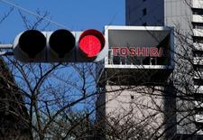 En la imagen, el logo de Toshiba Corp se ve tras un semáforo en su sede de Tokio, el 23 de enero de 2017. El consejo de administración de Toshiba Corp se reunirá el viernes para aprobar los planes para escindir a su negocio de semiconductores y espera recaudar más de 200.000 millones de yenes (1.800 millones de dólares) vendiendo un 20 por ciento de participación en el mismo, dijo una fuente con conocimiento directo del asunto.REUTERS/Toru Hanai