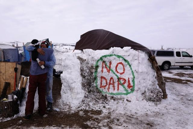 Benji Buffalo (R) greets a friend to his campsite inside of the Oceti Sakowin camp as ''water protectors'' continue to demonstrate against plans to pass the Dakota Access pipeline near the Standing Rock Indian Reservation, near Cannon Ball, North Dakota, U.S., December 2, 2016.  REUTERS/Lucas Jackson