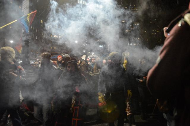 People walk through smoke from burning sage during a protest against President Donald Trump's executive order to allow the Keystone XL and Dakota Access pipelines in New York City, U.S. January 24, 2017. REUTERS/Stephanie Keith