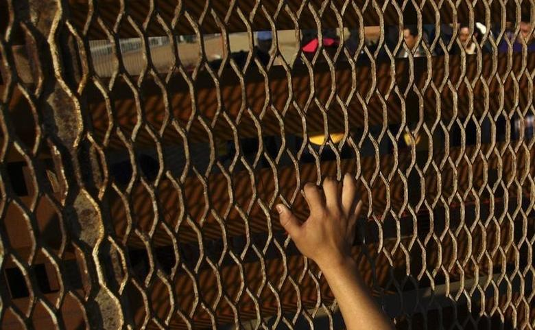 A man touches the double steel fence that separates San Diego and Tijuana at the border in Tijuana December 10, 2011.  REUTERS/Jorge Duenes