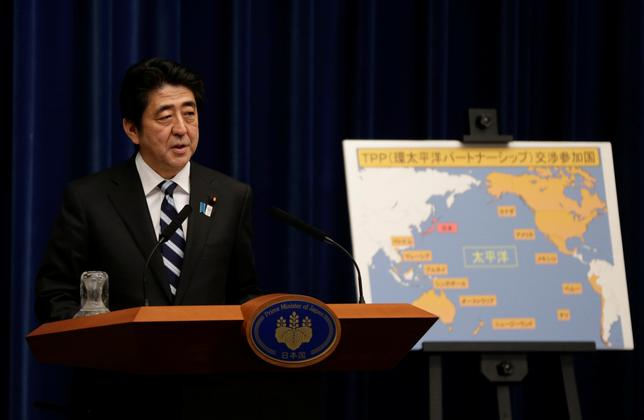 FILE PHOTO -  Japan's Prime Minister Shinzo Abe speaks next to a map showing participating countries in rule-making negotiations for the Trans-Pacific Partnership (TPP) during a news conference at his official residence in Tokyo March 15, 2013.   REUTERS/Toru Hanai/File Photo