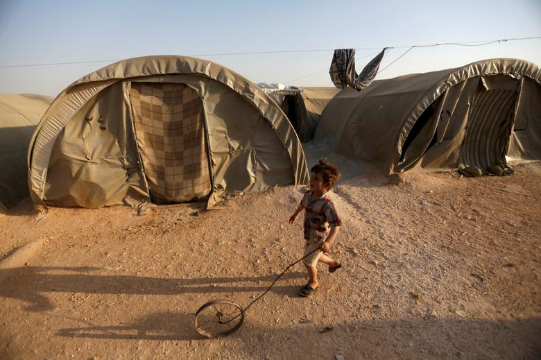 FILE PHOTO: An internally displaced Syrian boy plays with a wheel in Jrzinaz camp, in the southern part of Idlib, Syria, June 21, 2016. REUTERS/Khalil Ashawi/File Photo