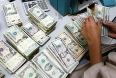A bank employee counts U.S. dollar notes at a Kasikornbank in Bangkok, Thailand, May 12, 2016. REUTERS/Athit Perawongmetha