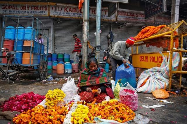 A woman makes flower garlands to sell in Old Delhi, India February 1, 2017. REUTERS/Cathal McNaughton