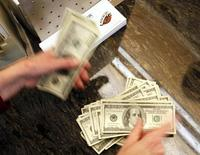 Four thousand U.S. dollars are counted out by a banker counting currency at a bank in Westminster, Colorado November 3, 2009.  REUTERS/Rick Wilking