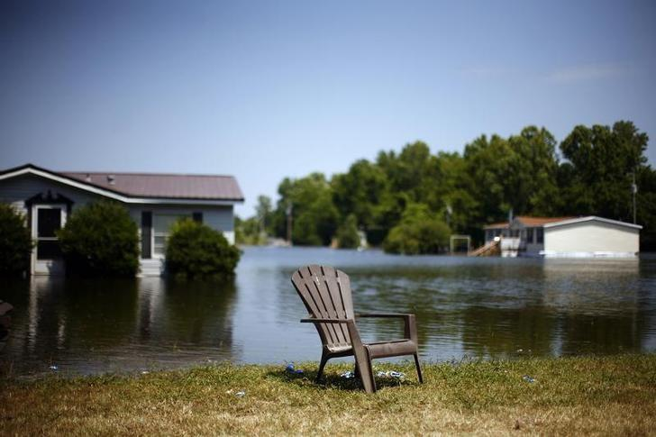 A chair is seen next to partially submerged houses in a flooded neighborhood in Vicksburg, Mississippi May 19, 2011.  REUTERS/Eric Thayer
