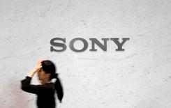 FILE PHOTO -  A reception staff walks under a logo of Sony Corp at its headquarters in Tokyo February 4, 2015.   REUTERS/Yuya Shino/File Photo