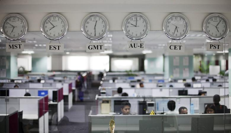 Workers are pictured beneath clocks displaying time zones in various parts of the world at an outsourcing centre in Bangalore, February 29, 2012. REUTERS/Vivek Prakash