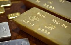 Золотые слитки. Золото в пятницу дешевеет, отступая от достигнутого накануне 11-недельного максимума перед выходом данных о числе рабочих мест в США за январь на фоне восстановления доллара к евро и иене.    REUTERS/Mariya Gordeyeva