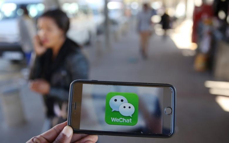 A WeChat logo is displayed on a mobile phone as a woman walks past as she talks on her mobile phone at a taxi rank in this picture illustration taken July 21, 2016.   REUTERS/Siphiwe Sibeko/Illustration/Files