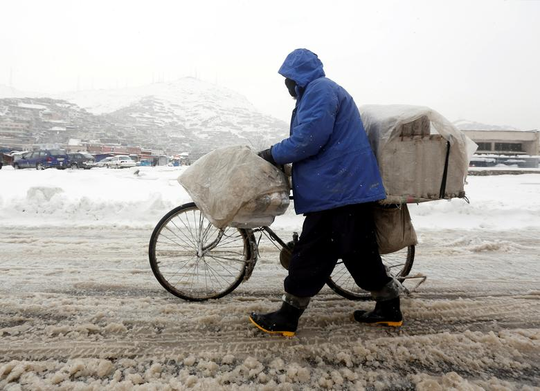 An Afghan man pushes his bicycle on a snowy day in Kabul, Afghanistan February 5, 2017. REUTERS/Omar Sobhani