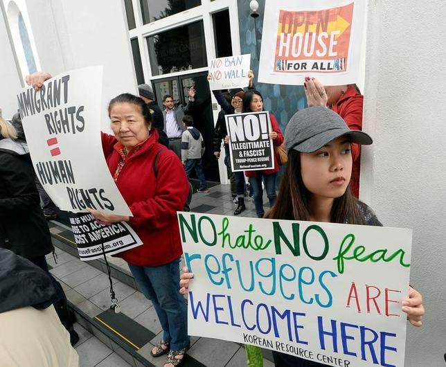 2月5日、アップル、グーグル、マイクロソフトなどのハイテク大手を含む100社近い米企業が、移民の米国への入国を制限する大統領令について、「米国のビジネスを著しく損なう」として、大統領令に反対する弁論趣意書を裁判所に提出した。写真は抗議を記した看板を持つ市民。ロサンゼルスで3日撮影(2017年 ロイター/Kevork Djansezian)