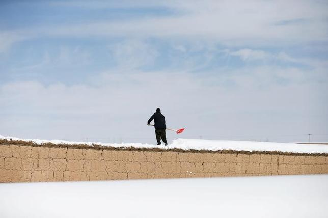 An Afghan man removes snow from his house wall on the outskirts of Kabul, Afghanistan February 6, 2017. REUTERS/Mohammad Ismail