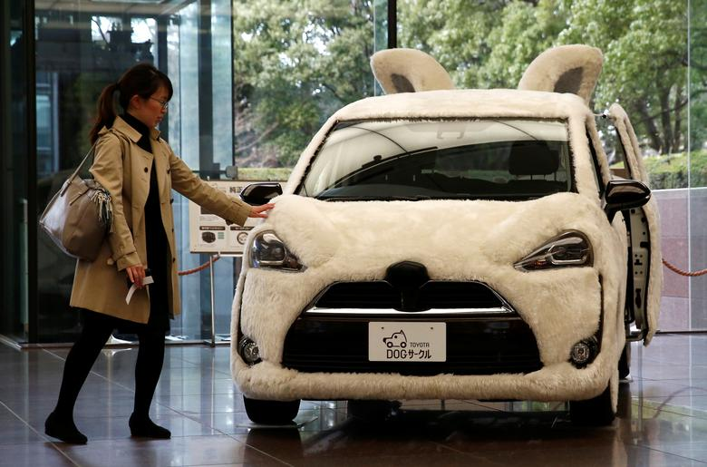 A woman touches Toyota's vehicle decorated as shape of dog at its headquarters in Tokyo, Japan, February 6, 2017.  REUTERS/Kim Kyung-Hoon