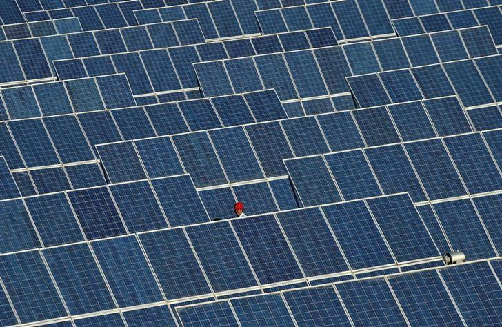 An employee walks between rows of solar panels at a solar power plant on the outskirts of Dunhuang, Gansu province, China, June 10, 2011.     REUTERS/Stringer/File Photo