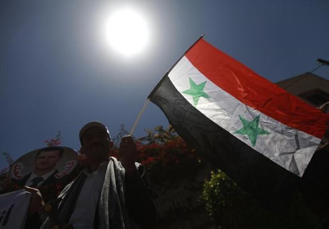 2月7日、国際人権団体アムネスティ・インターナショナルは、シリア政府が首都ダマスカス近郊セドナヤの軍刑務所で組織的な拷問を行い、最大1万3000人を秘密裏に絞首刑にしたとする報告書を発表した。写真はシリア国旗。イエメンの首都サヌアで2014年5月撮影(2017年 ロイター/Mohamed al-Sayaghi)