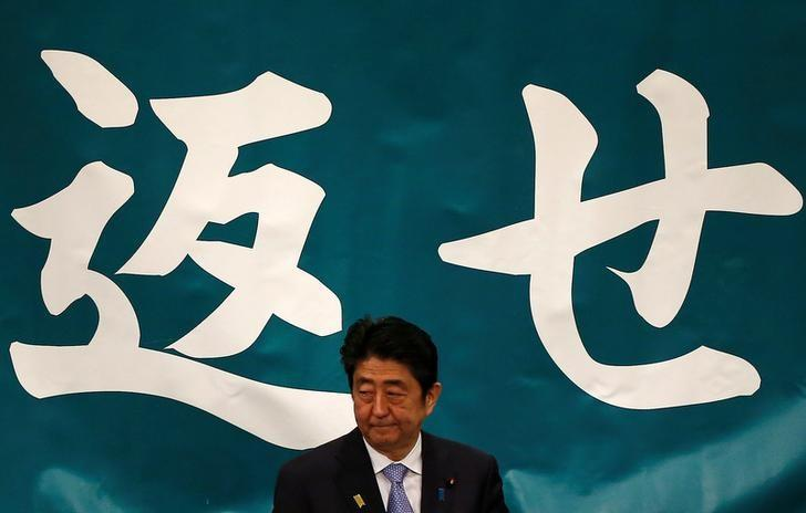 Japan's Prime Minister Shinzo Abe attends a Northern Territories Day rally to call on Russia to return a group of islands, known as the Northern Territories in Japan and the Southern Kuriles in Russia, in Tokyo, Japan February 7, 2017. The characters in the background read, ''return'', which is part of the phrase ''Return the four northern islands''. REUTERS/Issei Kato