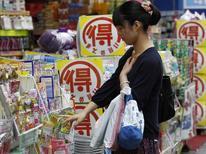 Женщина у стойки с товарами возле аптеки в Токио. 28 июня 2013 года. Члены совета управляющих Банка Японии отметили улучшение экспорта, потребительских расходов и капзатрат, но предупредили, что для роста инфляционных ожиданий может понадобиться время, свидетельствует протокол с мнениями чиновников, высказанными ими в ходе заседания регулятора 30-31 января. REUTERS/Yuya Shino