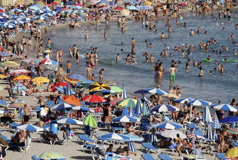 People sunbathe and swim on a beach in Benidorm, eastern Spain, August 20, 2011. REUTERS/Miguel Vidal