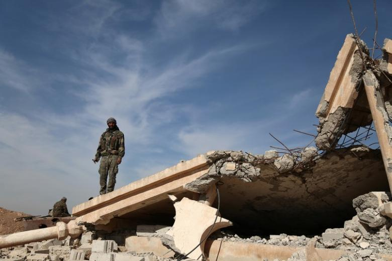 An Syrian Democratic Forces (SDF) fighter stands with his weapon on the rubble of a destroyed building, north of Raqqa city, Syria November 7, 2016. REUTERS/Rodi Said