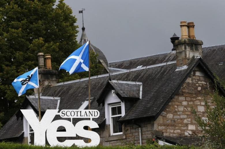 File photo: Scottish flags fly above a sign in support of the Yes campaign outside a house in Pitlochry , Scotland, September 16, 2014.  REUTERS/Russell Cheyne