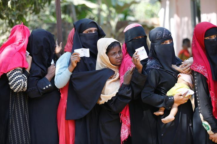 Rohingya women wait in a queue with vouchers to collect relief distributed by the Bangladesh Red Crescent Society at Kutupalang Unregistered Refugee Camp in Cox's Bazar, Bangladesh, February 6, 2017. REUTERS/Mohammad Ponir Hossain