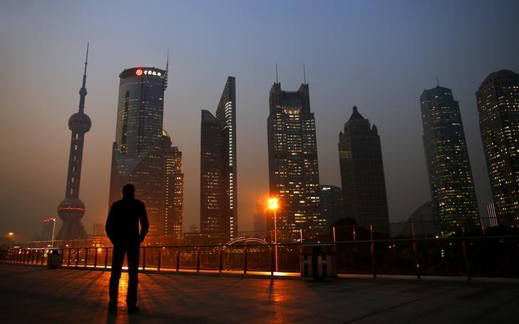 A man looks at the Pudong financial district of Shanghai November 20, 2013. With a shift in tone and language, China's central bank governor has dangled the prospect of speeding up currency reform and giving markets more room to set the yuan's exchange rate as he underlines broader plans for sweeping economic change. The central bank under Zhou Xiaochuan has consistently flagged its intention to liberalise financial markets and allow the yuan to trade more freely, even before the Communist Party's top brass unveiled late last week the boldest set of economic and social reforms in nearly three decades.   REUTERS/Carlos Barria (CHINA - Tags: BUSINESS CITYSCAPE TPX IMAGES OF THE DAY) - RTX15LH0
