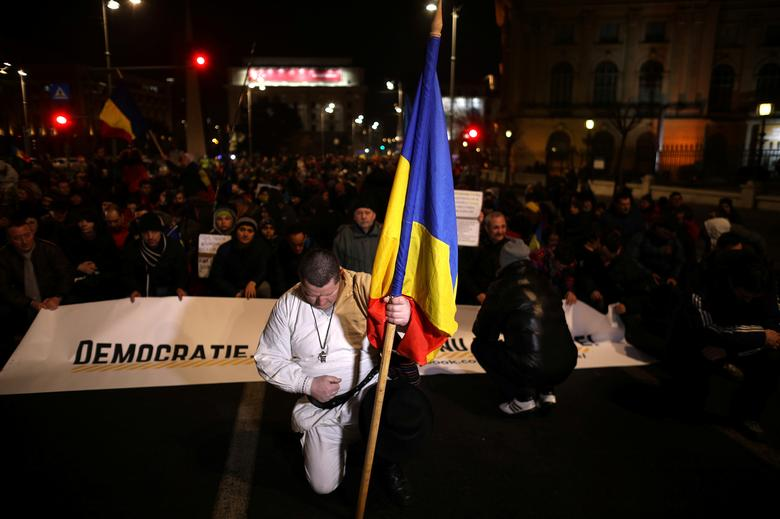 A protester holds a Romanian flag during a demonstration in Bucharest. REUTERS/Stoyan Nenov