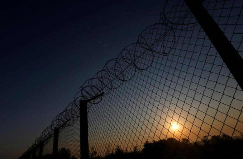 The sun rises along the Hungary and Serbia border fence near the village of Asotthalom, Hungary, October 2, 2016 as Hungarians vote in a referendum on the European Union's migrant quotas. REUTERS/Laszlo Balogh