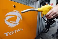 Un cliente tiene una estación de servicio en una estación Total en Niza, Francia. 9 de febero 2017.  La petrolera francesa Total dijo el jueves que está a la caza de activos de algunos rivales en dificultades, luego de reportar una ganancia neta mejor de la esperada en el cuarto trimestre gracias a recortes de costos y aumentar su dividendo.   REUTERS/Eric Gaillard - RTX309GN