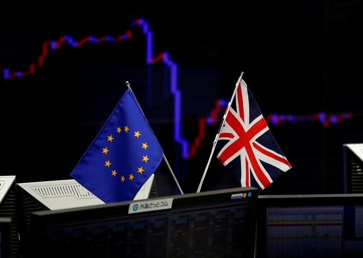 A British flag and an EU flag are seen in front of a monitor displaying a graph of the Japanese yen's exchange rate against the U.S. dollar at a foreign exchange trading company in Tokyo, Japan, June 27, 2016.  REUTERS/Toru Hanai
