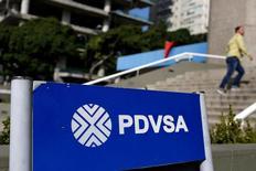 Логотип PDVSA в Каракасе. Государственная нефтяная компания Венесуэлы PDVSA на несколько месяцев задержала поставки нефти и топлива Китаю и России в рамках программы нефть в обмен на кредит, следует из внутренних документов компании, с которыми удалось ознакомиться Рейтер.   REUTERS/Carlos Garcia Rawlins