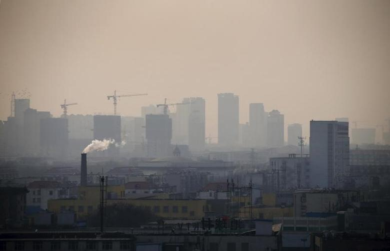 Smoke rises from a chimney among houses as new high-rise residential buildings are seen under construction on a hazy day in the city centre of Tangshan, Hebei province in this February 18, 2014 file photo. REUTERS/Petar Kujundzic/Files