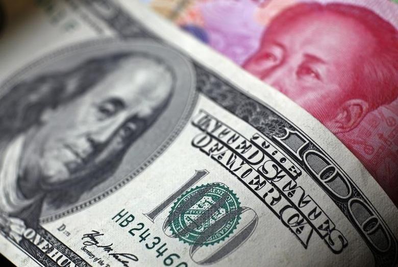 图为百元面值的美元和人民币纸币。REUTERS/Petar Kujundzic