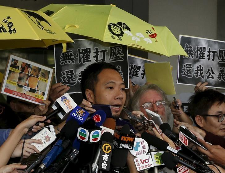 Protester Ken Tsang Kin-chiu, surrounded by supporters holding yellow umbrellas, symbols of the Occupy Central movement, and reporters, speaks outside a court in Hong Kong, China October 19, 2015. REUTERS/Bobby Yip/Files